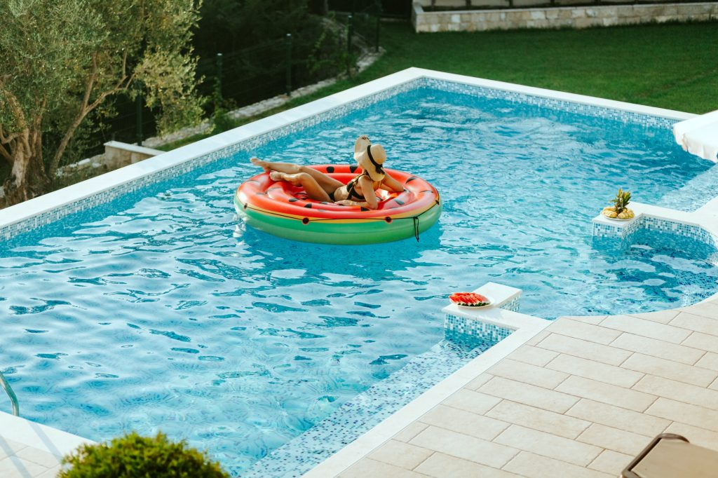 woman relax in swimming pool on inflatable pool toy at summer day